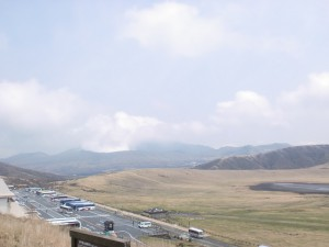 草千里展望所から見下ろす阿蘇火山博物館の駐車場と草千里の高原の画像