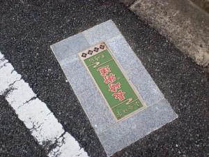 長崎街道八幡茶屋郵便局横の五差路付近に埋め込まれて長崎街道を示すプレートの画像